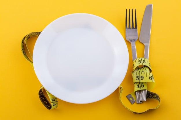 cubiertos-plato-blanco-cinta-metrica-sobre-amarillo-concepto-dieta-perdida-peso_78492-3736