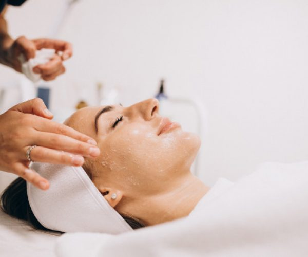 cosmetologa-limpiando-cara-mujer-salon-belleza_1303-16748