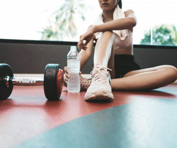 mujeres-sientan-relajan-despues-ejercicio-hay-botella-agua-pesas_1150-16431